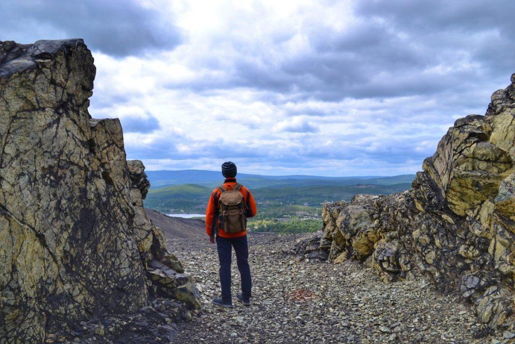 Человек стоит в расщелине горы