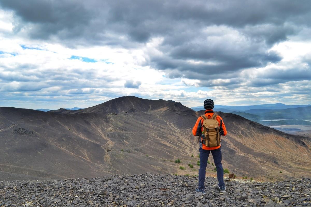Человек стоит на вершине холма