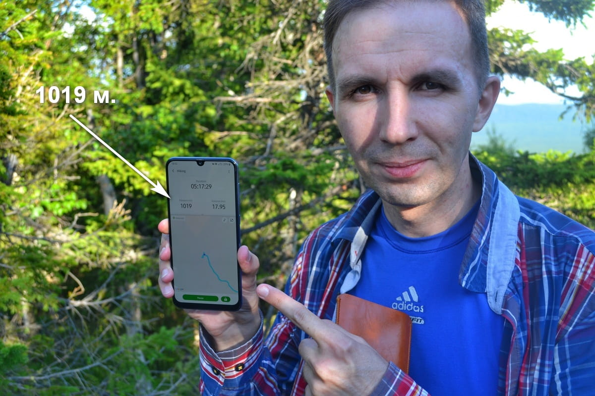 Александр Гусев держит в руке телефон с указателем высоты над уровнем моря
