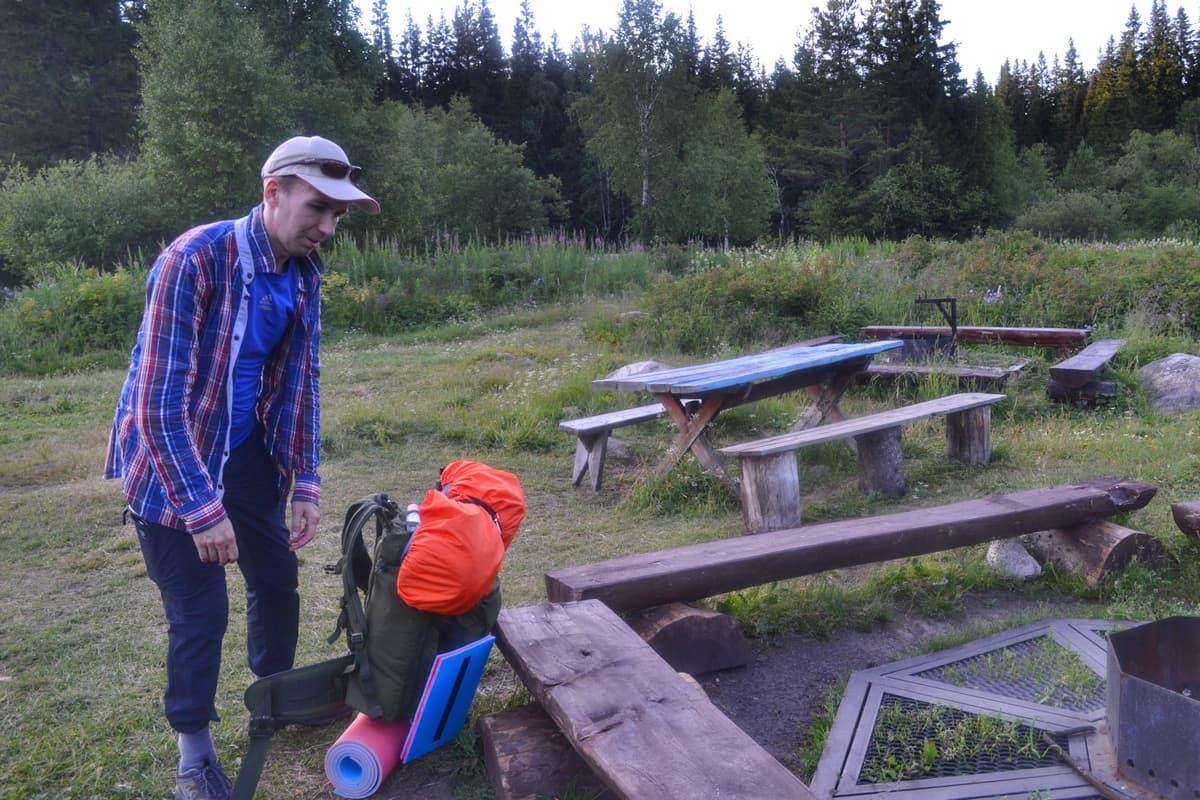 Турист на привале рядом с рюкзаком