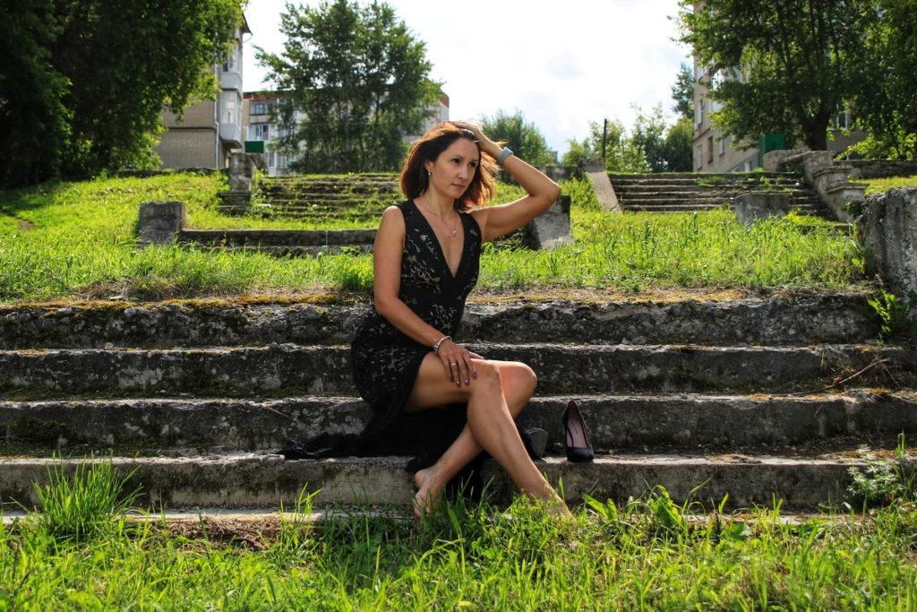 Женщина в платье сидит на ступенях лестницы на улице