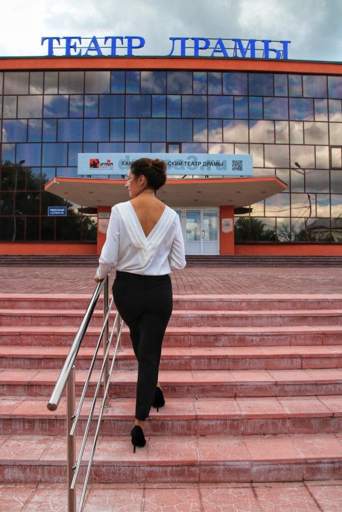 Женщина поднимается по ступеням к театру