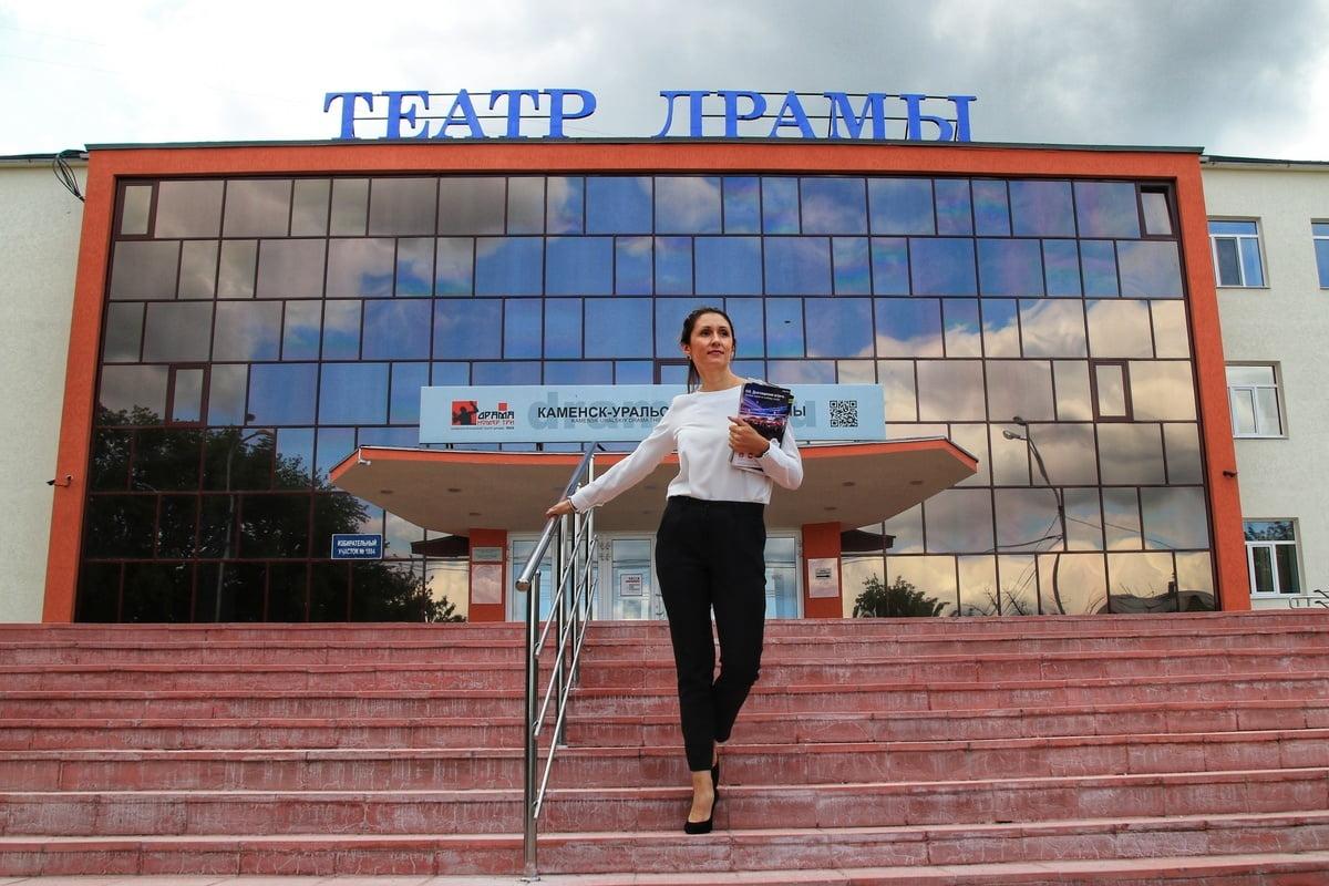 Женщина с журналами в руках спускается по лестнице