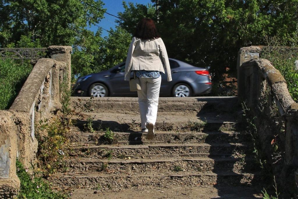 Девушка поднимается по ступеням лестницы