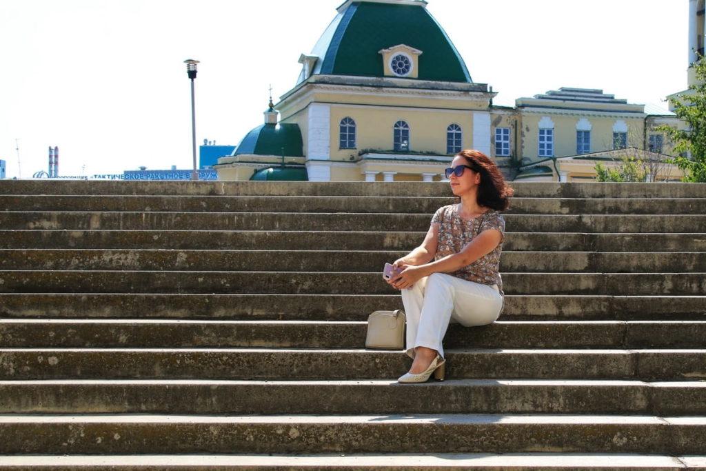 Девушка на ступенях лестницы напротив церкви