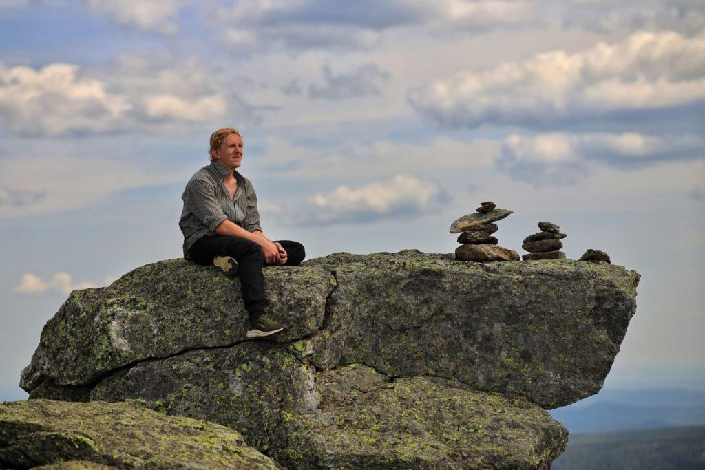 Турист сидит на скале на вершине горы Дальний Таганай