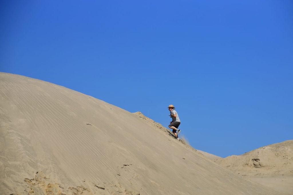 Фотосессия в пустыне, человек забегает на дюну