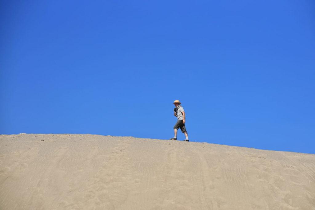 Фотосессия в пустыне, человек идёт по вершине дюны