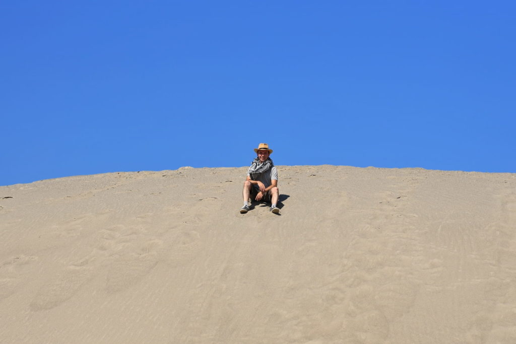 Фотосессия в пустыне, человек сидит на склоне дюны