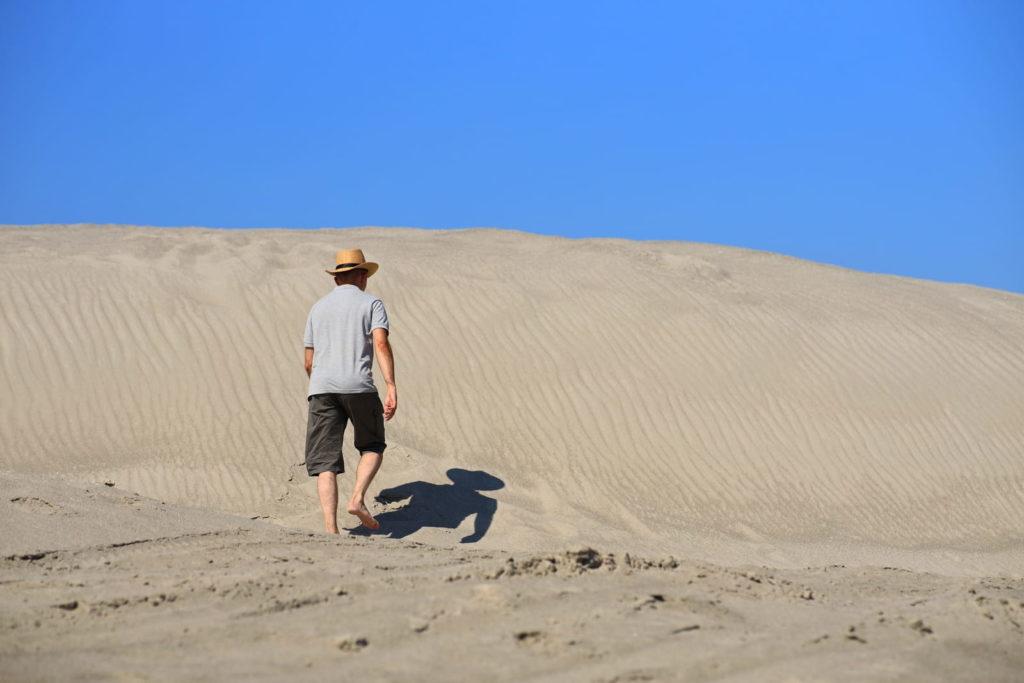 Фотосессия в пустыне, человек босиком идёт по песку