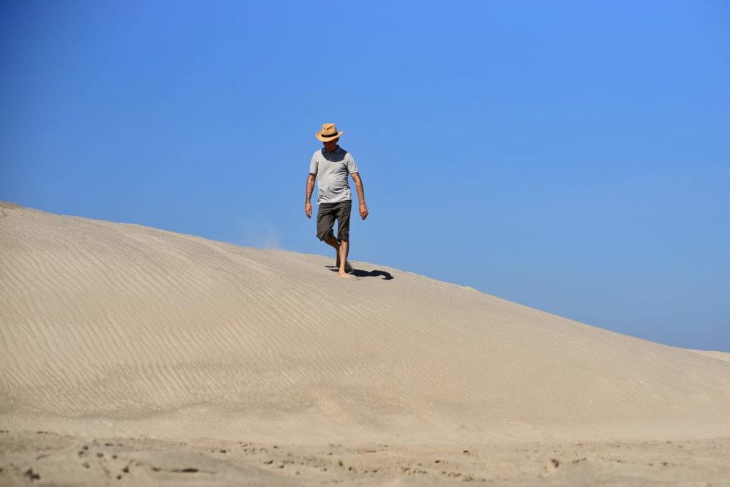 Фотосессия в пустыне, человек спускается по песку